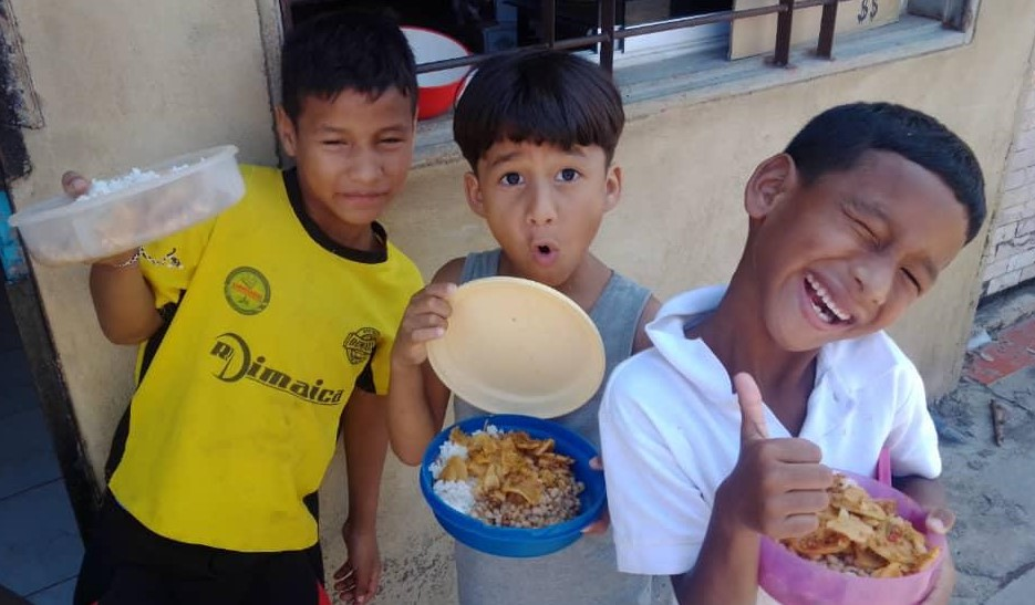 Smiling-Children-In-Venezuela-Holding-Plates-of-Food-With-Thumbs-Up